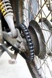 La ruota posteriore di un motociclo con una catena sporca Fotografie Stock Libere da Diritti