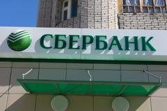 La Russia Berezniki- 13 agosto 2017 un segno con il logo del ramo di Sberbank della Russia contro il cielo blu ` S della Russia p fotografia stock libera da diritti