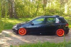 La Russia, Mosca - 1° giugno 2019: Volkswagen Golf nero Mk6 ha sintonizzato con ragtop e le ruote arancio Posizione che sintonizz fotografia stock libera da diritti