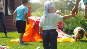 La Russia, Novosibirsk, il 23 luglio 2016 Bambini felici che giocano con gli animatori in costumi luminosi all'aperto sull'erba a Immagini Stock Libere da Diritti