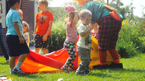 La Russia, Novosibirsk, il 23 luglio 2016 Bambini felici che giocano con gli animatori in costumi luminosi all'aperto sull'erba a Immagine Stock Libera da Diritti