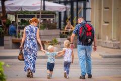 La Russia, Rostov On Don, il 9 settembre 2018: Passeggiata felice della famiglia con due bambini blondy svegli sulla via della ci fotografia stock