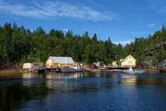 La Russie, fjord au paysage du nord grave de côte de mer blanche avec un village de pêche typique dans le nord de la Russie Petit Photos stock