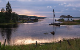 La Russie, nuit blanche au paysage du nord grave de côte de mer blanche avec un village de pêche typique dans le nord de la Russi Photos stock