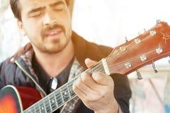La Russie, Riazan - 12 04 2015 - L'homme mûr bel dans des vêtements sport sourit tout en jouant la guitare photos libres de droits