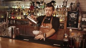 La Russie Rosa Khutor - février 2018 : le barman verse le cocktail alcoolique dans le verre banque de vidéos