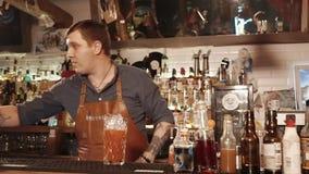 La Russie Rosa Khutor - février 2018 : un jeune barman ajoute la glace à une boisson de tomate banque de vidéos