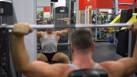 La Russie, Togliatti - 20 septembre 2018 : L'homme musculaire forme ses épaules avec un barbell dans le gymnase Santé et forme ph clips vidéos