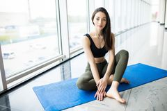 La séance attrayante de jeune femme détendent dans le tapis sur le plancher après la formation de yoga dans le gymnase image libre de droits