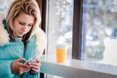 La séance blonde de fille dans un café Photo stock
