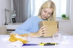 La séance blonde enthousiaste et l'ouverture de femme une boîte, un colis, objets sur la table sont dans le désordre photo stock