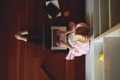 La séance blonde mignonne sur le plancher sur ses genoux est un ordinateur, elle regarde le courrier Photos stock