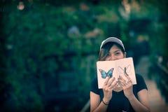 La séance d'adolescente de femme de hippie apprécient le livre de lecture au pilier Concept de livre de lecture de jeune femme, r Photographie stock libre de droits