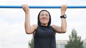 La séance d'entraînement de femme de forme physique essaye de faire des exercices sur une barre horizontale dehors photos stock