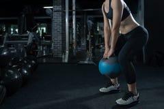 La séance d'entraînement d'exercice de femme au sport de formation de forme physique de gymnase avec l'haltérophilie de kettlebel photos stock