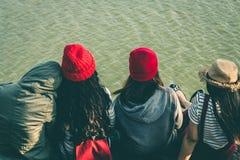 La séance de touristes de la femme sur la rivière entourée par des rivières Photo stock