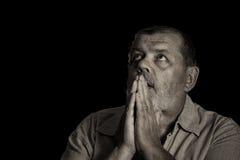 La sépia a modifié la tonalité l'image d'un homme supérieur de prière recherchant Photo stock