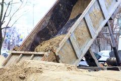 La sabbia è versata dal corpo del camion fotografia stock libera da diritti