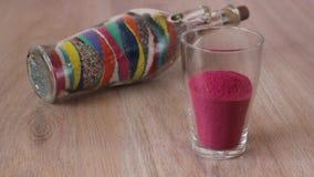 La sabbia colorata è versata nel vetro e nelle conchiglie disposti sulla cima stock footage
