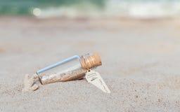 La sabbia e la conchiglia in bottiglia hanno messo sopra la spiaggia fotografie stock libere da diritti