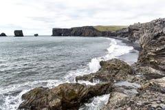 La sabbia nera vulcanica e le rocce vulcaniche sull'Islanda tirano fotografia stock
