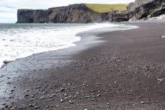 La sabbia nera vulcanica e le rocce vulcaniche sull'Islanda tirano fotografia stock libera da diritti