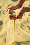 La sabbia versa dalle mani femminili fotografia stock