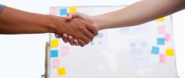 La sacudida de los hombres de negocios entrega la tabla en la reunión con el espacio de la copia con el whiteboard lleno de fondo foto de archivo