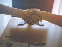La sacudida de la mujer y del hombre entrega la tabla de la oficina en luz anaranjada brillante imagenes de archivo