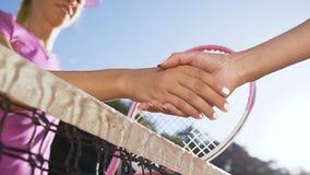La sacudida femenina de los jugadores de tenis entrega la red de la pista de tenis almacen de video