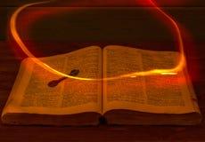 La Sagrada Biblia abierta está en la tabla Clave antiguo Un fuego que vuela sobre la biblia ilumina sus páginas imágenes de archivo libres de regalías