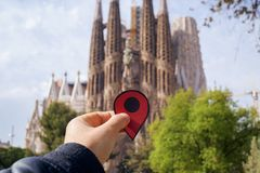La Sagrada Familia in Barcelona, Spain. BARCELONA, SPAIN - APRIL 6, 2018: Closeup of the hand of young caucasian man with a red marker in front of the famous La Stock Photo