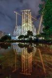 La Sagrada Familia - Barcelona, Spain. La Sagrada Familia illuminated at night, reflecting in the water. The cathedral was designed by Antoni Gaudi and has been Stock Image