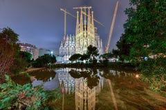 La Sagrada Familia - Barcelona, Spain. La Sagrada Familia illuminated at night, reflecting in the water. The cathedral was designed by Antoni Gaudi and has been Royalty Free Stock Photo