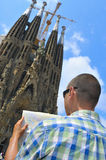 La Sagrada Familia in Barcelona, Spain. BARCELONA, SPAIN - JULY 14: Tourist with a city map in front of La Sagrada Familia on July 14, 2014 in Barcelona, Spain Stock Image