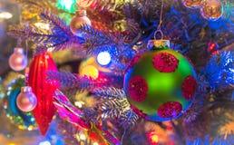 La saison des vacances, décorations d'arbre de Noël rougeoient sous les lumières lumineuses et vives, colorées sur un arbre d'int Image libre de droits