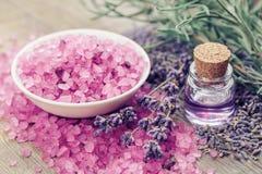 La sal del mar, la botella de aceite esencial y la lavanda florece Imágenes de archivo libres de regalías