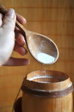 La sal en la cuchara de madera llevó a cabo a disposición la colada en un barril de madera fotografía de archivo