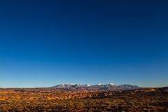 La Sal Mountains and the moon. Evening shot of the La Sal Mountains across the petrified dunes of Arches National Park stock images