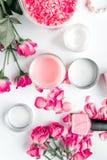 La sal y la crema de Rose para el clavo cuidan en balneario en la opinión superior del fondo blanco Foto de archivo