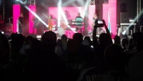 La sala da concerto di salto del rockband delle mani degli aumenti del pubblico felice del fondo del video di movimento lento pro archivi video