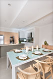 La sala da pranzo moderna ha installato con le candele che infiammano davanti alla cucina Immagine Stock Libera da Diritti
