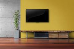 La sala de estar llevó la TV en la pared amarilla con el furnit de madera de los medios de la tabla Foto de archivo