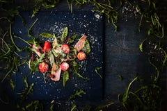 La salade avec du jambon fumé et l'arugula sur l'obscurité a rayé la table Photos libres de droits