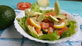 La salade avec le citron cru de fraîcheur d'avocat de poissons rouges huile la tomate de nutrition clips vidéos