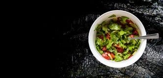 La salade d'été des tomates, des concombres et du chou a assaisonné avec du vinaigre, fond noir avec l'espace de copie, vue supér Images stock