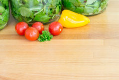 La salade dans le stockage en verre cogne sur le plan de travail en bois Copiez l'espace photos libres de droits