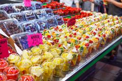 La salade de fruits a arrangé dans des tasses en plastique sur un marché Photo stock