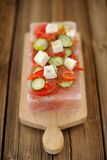 La salade de légume et de fromage a servi sur un bloc sur le rose de l'Himalaya s Photographie stock