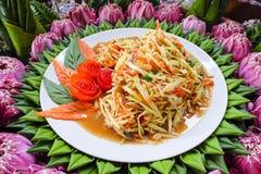 La salade de papaye est dans un plat blanc avec une feuille de banane images libres de droits